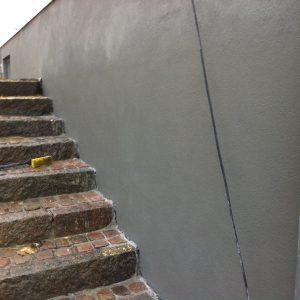 Trappenedgang: Udbedring af skader og pudsning af væg ved trappenedgang.